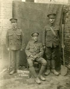 Three British artillerymen photographed in a makeshift studio near the front
